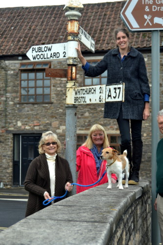 Lydia Robinson (on wall), Meg Thomas and Janette Stephenson with A37 finger post ready for makeover.
